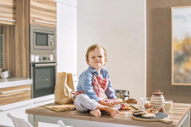 Szczęśliwe słodkie i piękne dziecko uśmiecha się w domu bawiąc się w kuchni