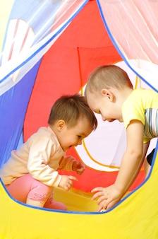 Szczęśliwe, śmiejące się dzieci bawią się w małym domku zabawki.