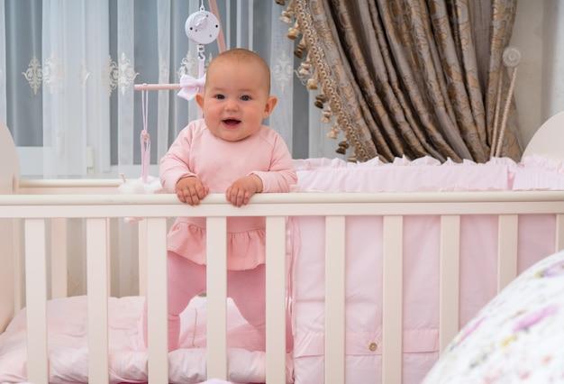 Szczęśliwe, śmiejące się dziecko stojące w łóżeczku w różowej scenie sypialni.