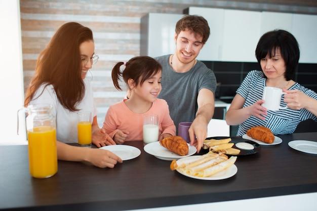 Szczęśliwe śniadanie dużej rodziny w kuchni. rodzeństwo, rodzice i dzieci, matka i babcia. ojciec i córka. wszyscy jedzą rano, rozmawiają i dobrze się bawią.