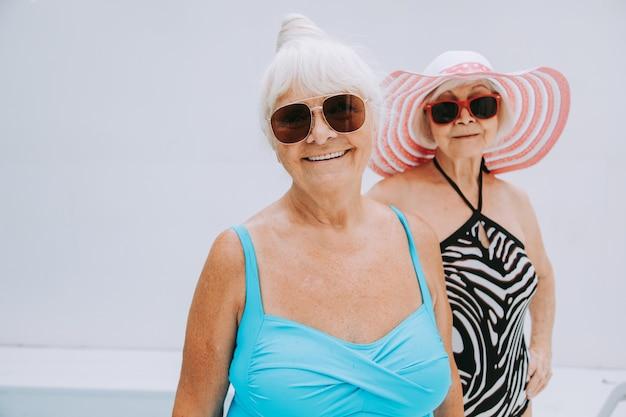 Szczęśliwe starsze kobiety bawiące się na basenie - starsi przyjaciele relaksują się na imprezie przy basenie