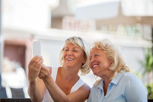 Szczęśliwe starsze kobiety robi mobilnemu selfie