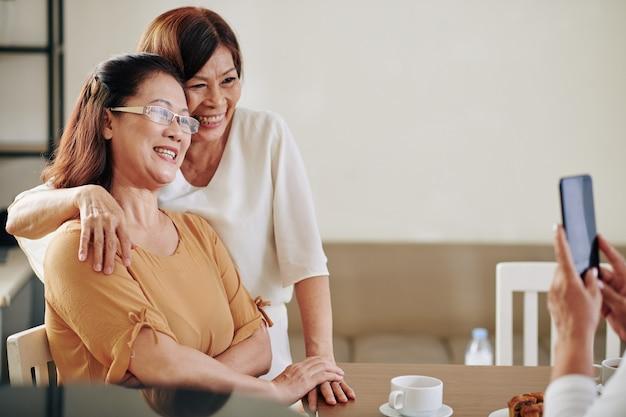 Szczęśliwe starsze wietnamskie koleżanki przytulające się i pozujące do zdjęcia na smartfonie
