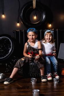 Szczęśliwe stylowe dzieciaki w warsztacie samochodowym wśród opon i kół