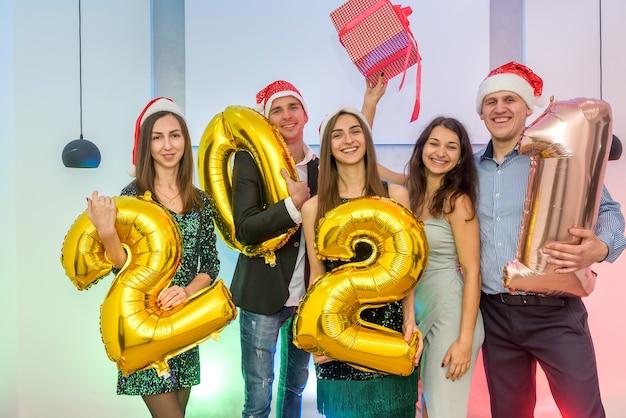 Szczęśliwe towarzystwo przyjaciół trzymających balony na powietrze 2021 podczas obchodów nowego roku