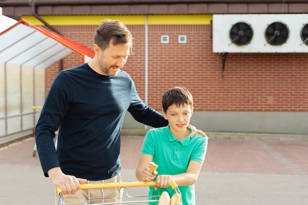 Szczęśliwe towarzystwo taty i jego syna wraz z koszykiem wychodzą z supermarketu, spędzają czas, koncepcja samotnego ojca
