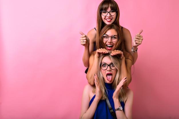 Szczęśliwe trzy dziewczyny przytulają się i dobrze się bawią, pozytywne szalone emocje, cele przyjaźni, przezroczyste okulary, jasne ubrania i różowa przestrzeń.
