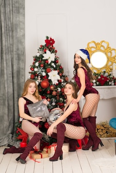 Szczęśliwe trzy piękne dziewczyny o innym kolorze włosów, śnieżna dziewczyna w strojach świątecznych, torba na prezent.