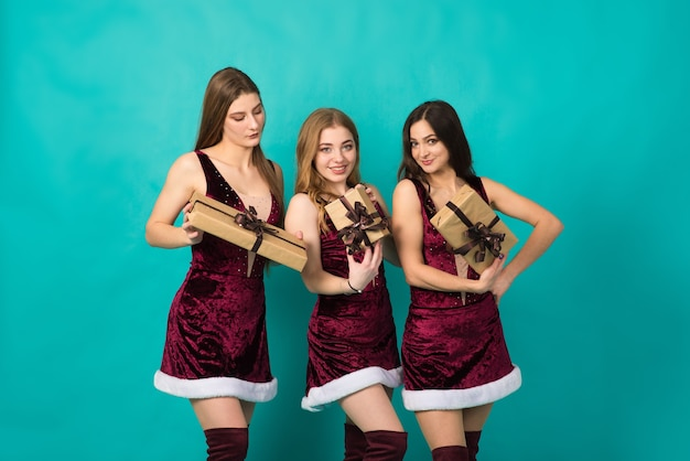 Szczęśliwe trzy piękne dziewczyny o innym kolorze włosów, śnieżna dziewczyna w strojach świątecznych z torbą na prezent.