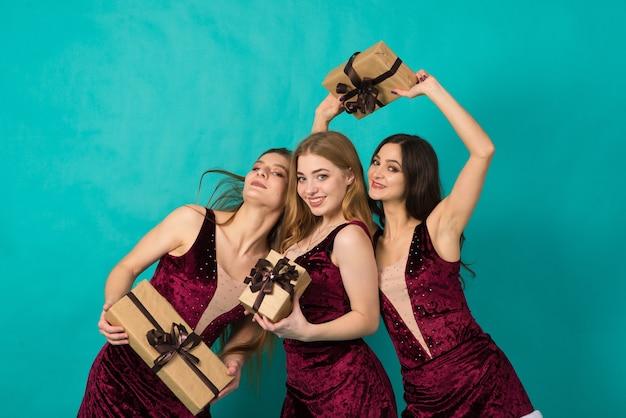 Szczęśliwe trzy piękne dziewczyny o różnym kolorze włosów, śnieżna dziewica w świątecznych kostiumach z torbą na prezent.