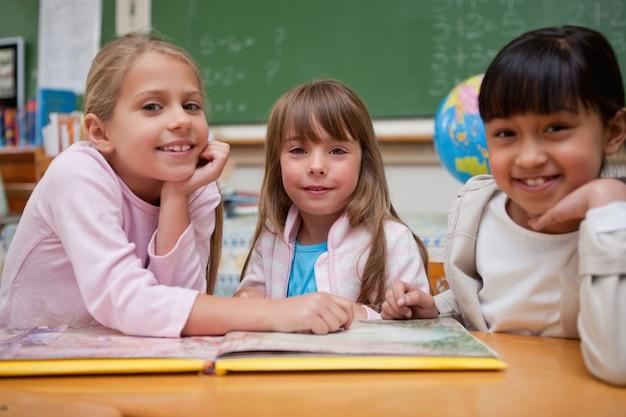 Szczęśliwe uczennice czytając bajkę ich kolega z klasy
