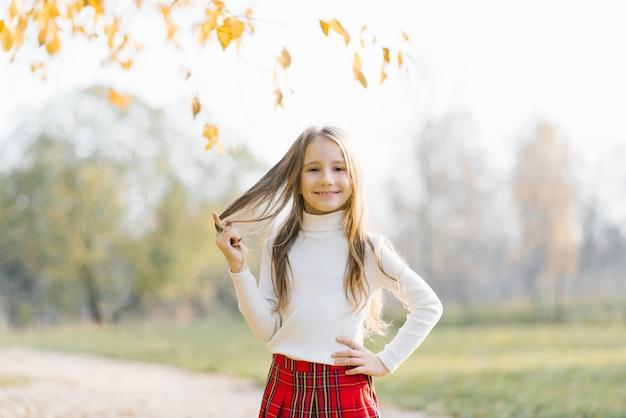 Szczęśliwe uśmiechnięte dziecko dziewczyny z żółtymi jesiennymi liśćmi w jesiennym lesie miejskim