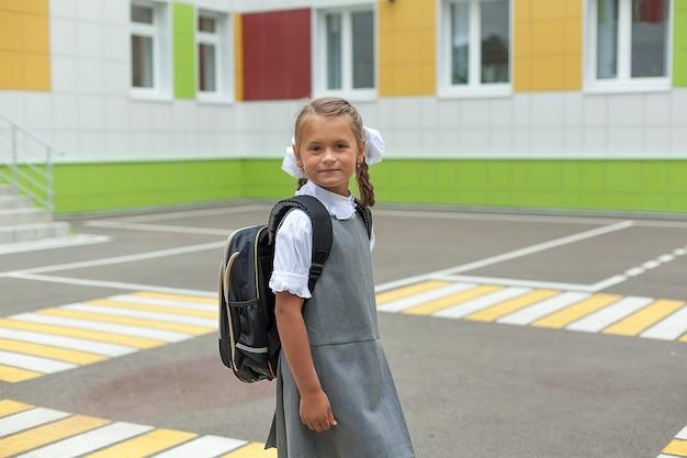 Szczęśliwe, uśmiechnięte dziecko idzie do szkoły po raz pierwszy