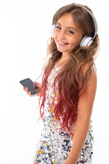 Szczęśliwe uśmiechnięte dziewczyny słuchają muzyki przez słuchawki