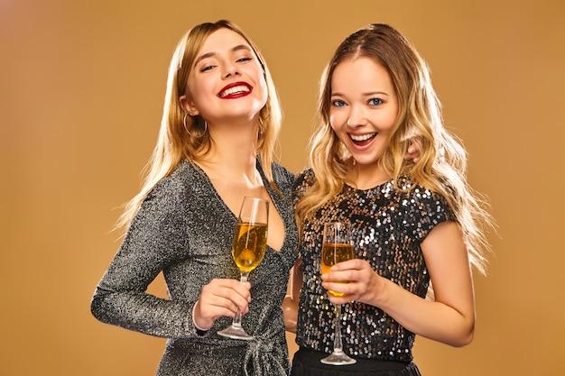 Szczęśliwe uśmiechnięte kobiety w stylowych czarujących sukniach z kieliszkami do szampana
