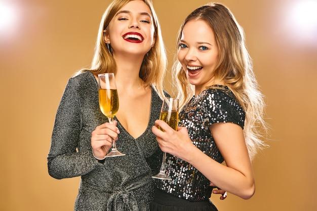 Szczęśliwe uśmiechnięte kobiety w stylowych czarujących sukniach z szampańskimi szkłami na złotej ścianie