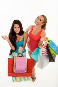 Szczęśliwe uśmiechnięte kobiety z torbami na zakupy.