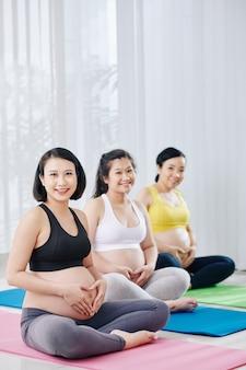 Szczęśliwe uśmiechnięte młode azjatki siedzące na macie do jogi w klasie sportowej i robiące kształt serca rękami
