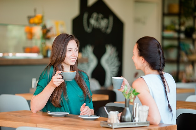 Szczęśliwe uśmiechnięte młode kobiety z filiżankami przy kawiarnią. koncepcja komunikacji i przyjaźni