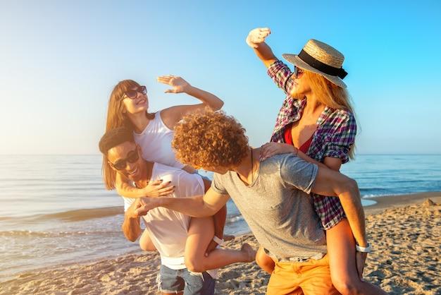 Szczęśliwe uśmiechnięte pary bawiące się na plaży
