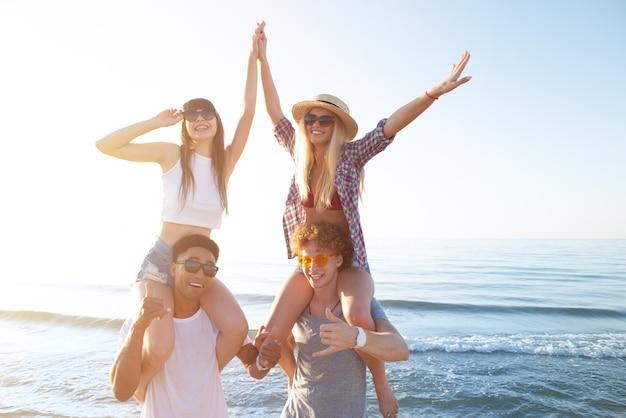 Szczęśliwe uśmiechnięte pary bawiące się na słonecznej plaży