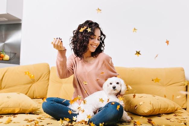 Szczęśliwe weekendy, prawdziwe pozytywne emocje młodej radosnej kobiety z obciętymi kręconymi włosami bawiącej się z małym psem w spadających złotych świecidełkach na kanapie w nowoczesnym mieszkaniu