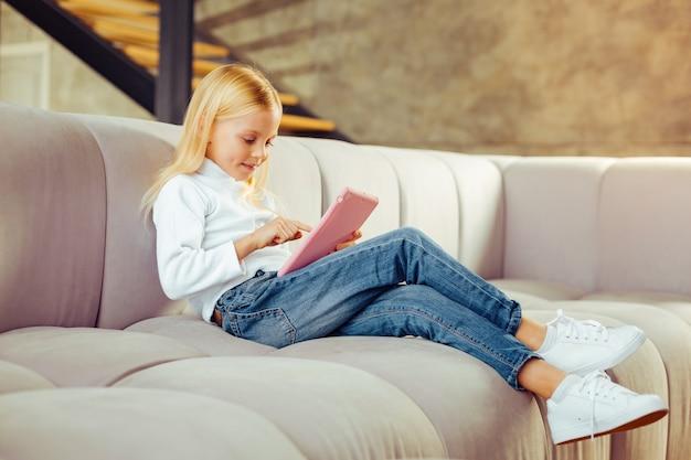 Szczęśliwe weekendy. wesoła dziewczyna wyrażająca pozytywne nastawienie, patrząc na ekran swojego gadżetu