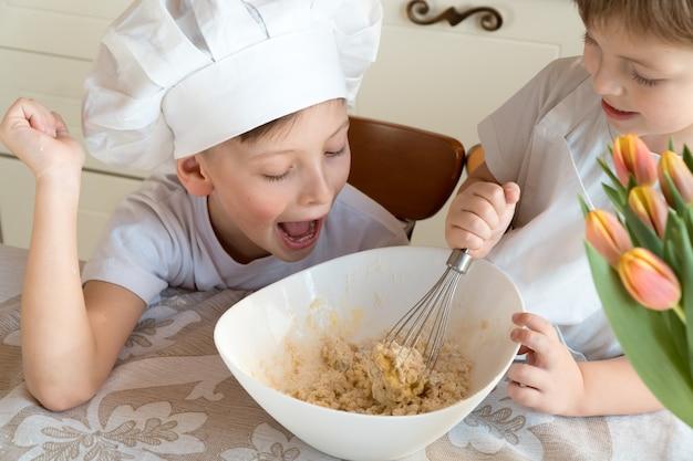 Szczęśliwe wesołe dzieciaki robiące ciasto w domu w kuchni