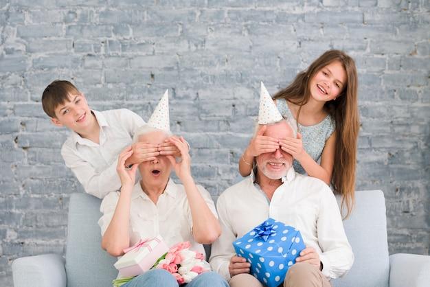 Szczęśliwe wnuki zasłaniające oczy dziadków na przyjęciu urodzinowym