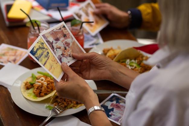 Szczęśliwe wspomnienia. kobieta trzymająca w dłoniach dwie fotografie z wakacji, patrząc na nie podczas lunchu.