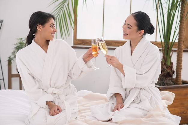 Szczęśliwe wydarzenie. wesoły lesbijki brzęk kieliszkami z szampanem podczas uroczystości