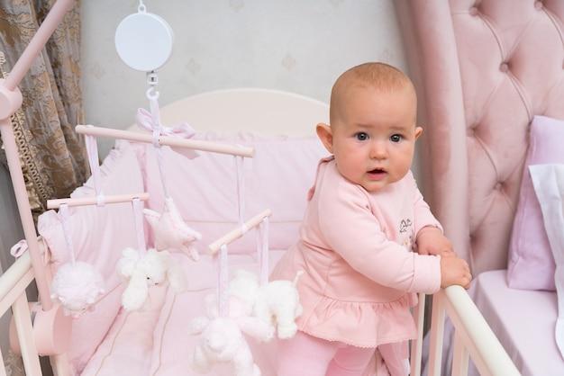 Szczęśliwe, zaciekawione niemowlę w różowym łóżeczku i sypialni z wiszącą karuzelą.