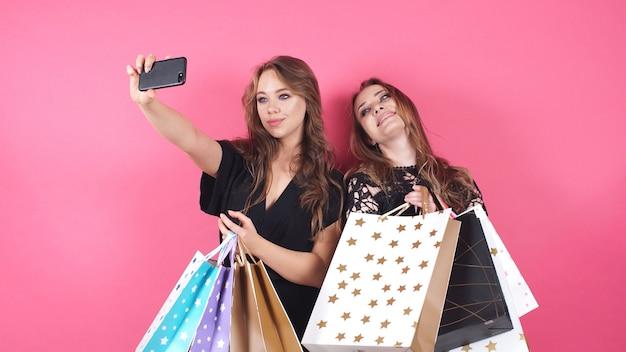 Szczęśliwe zakupy dziewczyny biorą selfies na odosobnionym tle