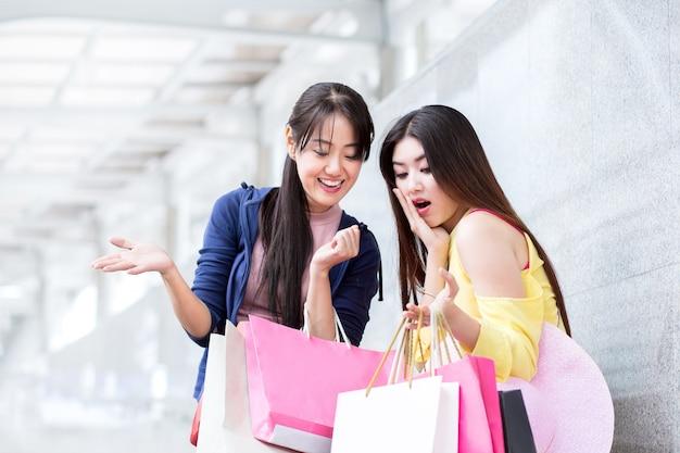 Szczęśliwe zakupy kobiety lub kobieta z przyjacielem, z torbą na zakupy w letniej sprzedaży sklepu w centrum miasta