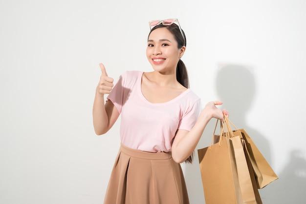 Szczęśliwe zakupy młoda kobieta pokazuje kciuk w górę z torbami - na białym tle, azjatycki model