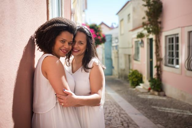 Szczęśliwe zamężne kobiety czule przytulające się na ulicy. kochające kobiety w sukniach ślubnych z bukietami czule przytulające