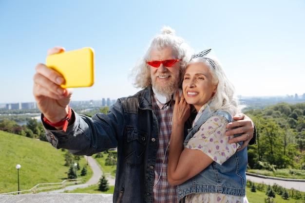 Szczęśliwe zdjęcia. zachwycona para w podeszłym wieku robi sobie selfie podczas wspólnego spaceru