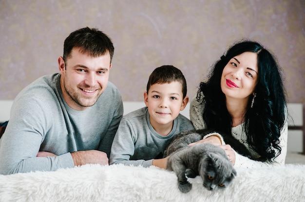 Szczęśliwe zdjęcie rodzinne. mąż, żona i syn przytulający się w domu. szczęśliwy syn przytula mamę i tatę, ciesząc się razem wakacjami.
