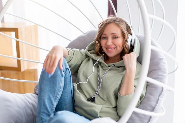 Szczęśliwe zęby uśmiech kobieta słuchać muzyki słuchawki kaukaska kobieta cieszyć się podcastem lub audiobookami podczas odpoczynku w fotelu na poddaszu ubrany w niebieskie dżinsy i oversize z kapturem