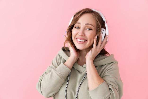 Szczęśliwe zęby uśmiech kobieta słuchaj muzyki słuchawki kaukaska kobieta ciesz się podcastem lub audiobookami ubrany oversize bluza z kapturem różowe tło zbliżenie portret