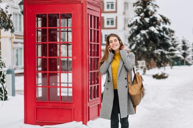 Szczęśliwe zimowe chwile wesoła modna młoda kobieta rozmawia telefon na ulicy w pobliżu czerwonej budki telefonicznej. zimowa mroźna pogoda, śnieg, pozytywne prawdziwe emocje, uśmiech. miejsce na tekst.