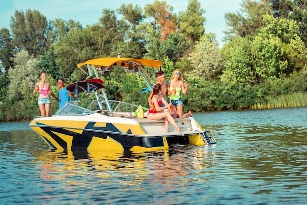 Szczęśliwe życie. towarzystwo dobrych przyjaciół cieszących się wolnym czasem podczas picia i rozmowy na łódce