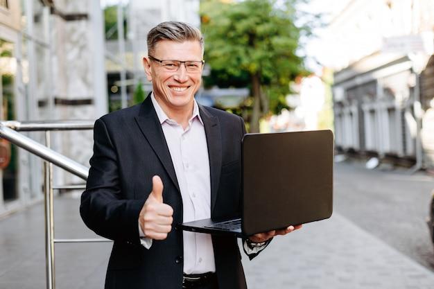 Szczęśliwego biznesmena mienia otwarty laptop, ono uśmiecha się z kciukiem up