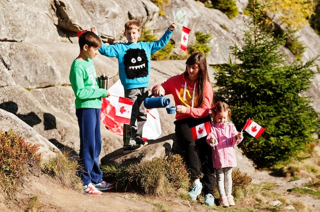 Szczęśliwego dnia kanady. rodzina matki z trójką dzieci organizuje wielkie święto flagi kanadyjskiej w górach.