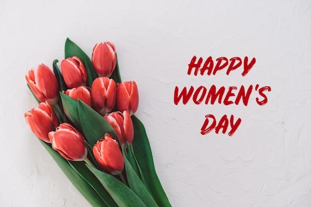 Szczęśliwego dnia kobiet. bukiet czerwonych tulipanów na komodzie w salonie.