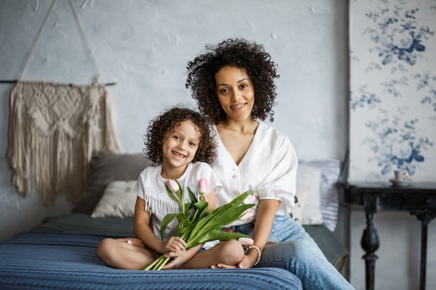 Szczęśliwego dnia kobiet! tulipany mamy i córki. mama i dziewczyna uśmiechają się z aparatami o afroamerykańskim wyglądzie.
