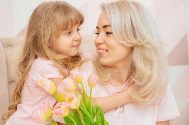Szczęśliwego dnia matki. córeczka gratuluje mamie i daje jej bukiet kwiatów tulipanów w różowym salonie w ich domu.