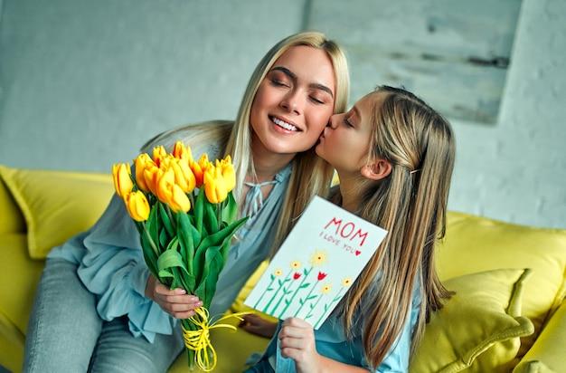 Szczęśliwego dnia matki! córka dziecka gratuluje mamie, całuje i daje bukiet kwiatów tulipanom
