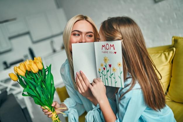 Szczęśliwego dnia matki! córka dziecka gratuluje mamie i daje jej kwiaty tulipany i pocztówkę. mama i dziewczyna uśmiechając się i przytulając. rodzinne wakacje i razem.