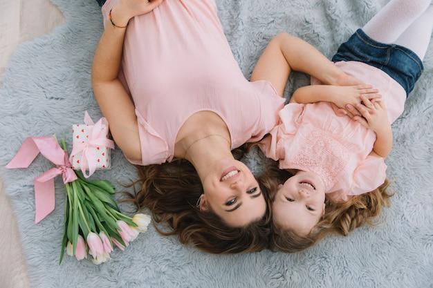 Szczęśliwego dnia matki. córka dziecka gratuluje mamie i daje jej kwiaty tulipany i prezent